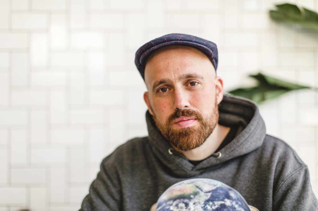 Author Justin Barker wearing grey sweatshirt and hat in front of a white tile background.